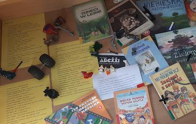 W gablocie znajduje się 8 kolorowych okładek książek oraz trzy arkusze żółtego papieru na której umieszczone są tytuły książek. Obok kartek leżą części do klocków Lego.