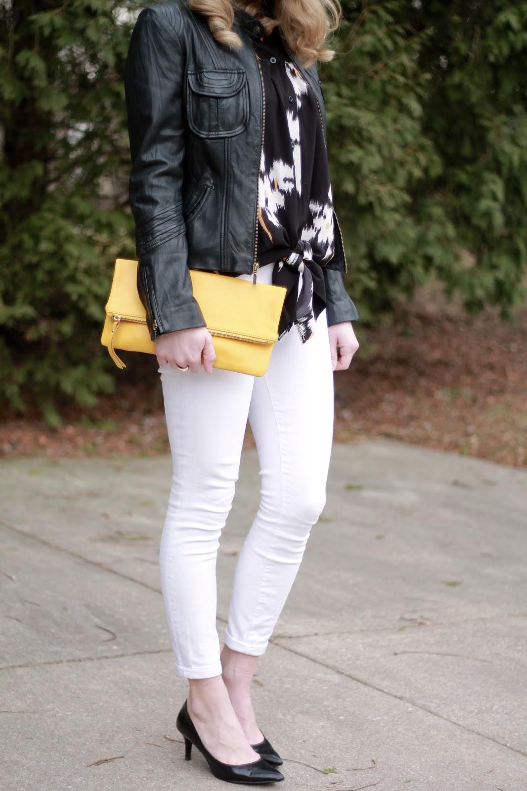 black floral tie top, black moto jacket, white jeans, black heels, yellow clutch