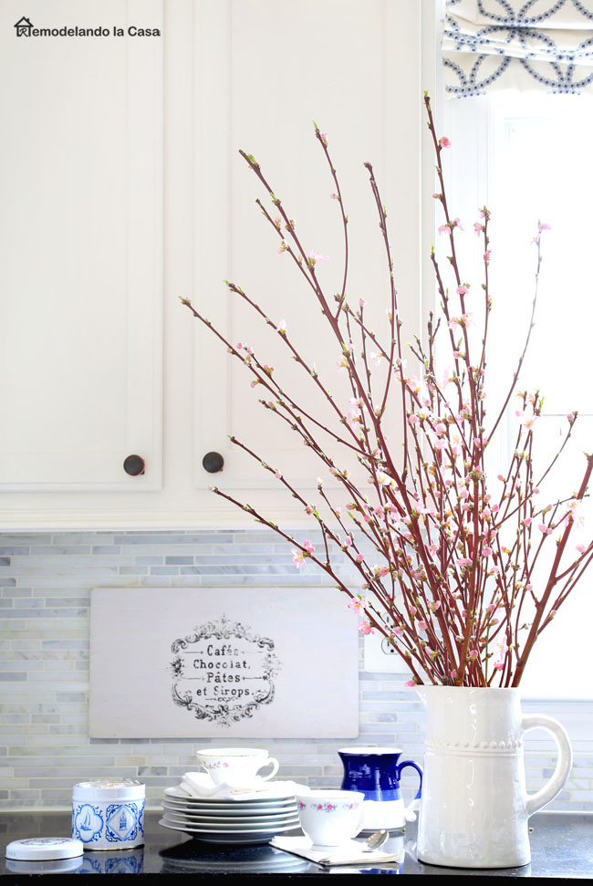 Kitchen counter with pink flowering branches in a pitcher, plates and sign on backsplash