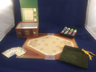 The components of War Chest. A game board, with several cards arrayed to one side, the velvet bags on the other side, a tray of tokens behind it, and the game box lying open nearby.