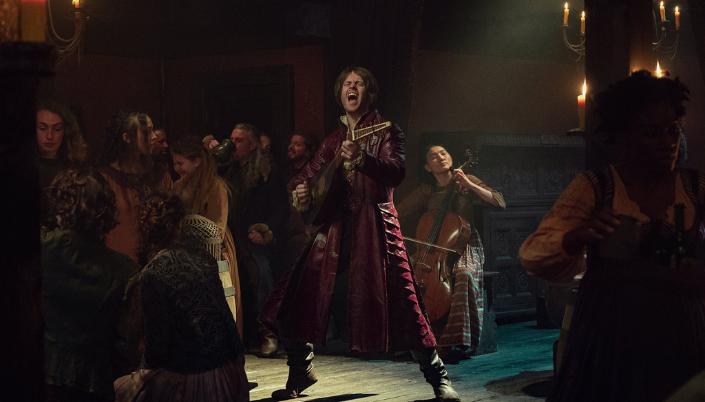 Imagem: o bardo Jaskier, interpretado por Joey Batey, um homem branco de cabelos castanhos em roupas cor de vinho, tocando um tipo de viola e cantando, acompanhado por várias mulheres tocando violinos e com uma multidão em roupas medievais cantando junto.