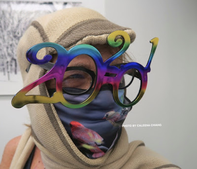 "This photo features a woman wearing ""costume glasses"" New Year's glasses for 2021. They are made from a metallic plastic material comprised of a several colors including shades of blue, shades of pink and shades of yellow."
