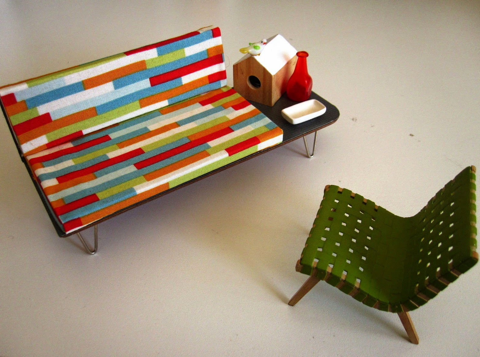 Mid century modern miniature sofa with attached coffee table and Jens Risom armchair, On the coffee table are mid century accessories including a bird house, bird, bottle and dish.
