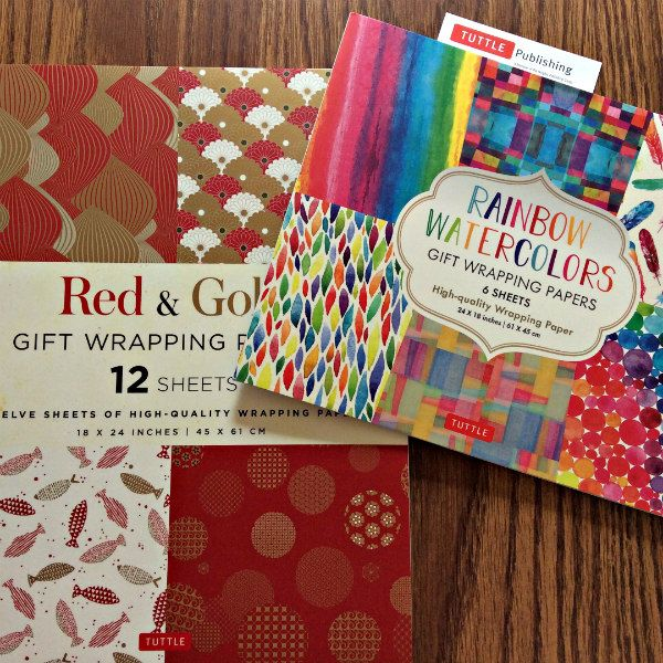 two books of wrapping paper sheets - red and gold, and rainbow watercolor collections