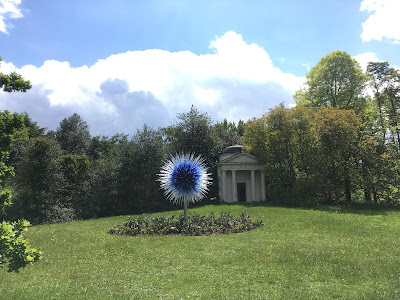 sapphire star galss sculpture in foreground, greek style temple, and trees in the background
