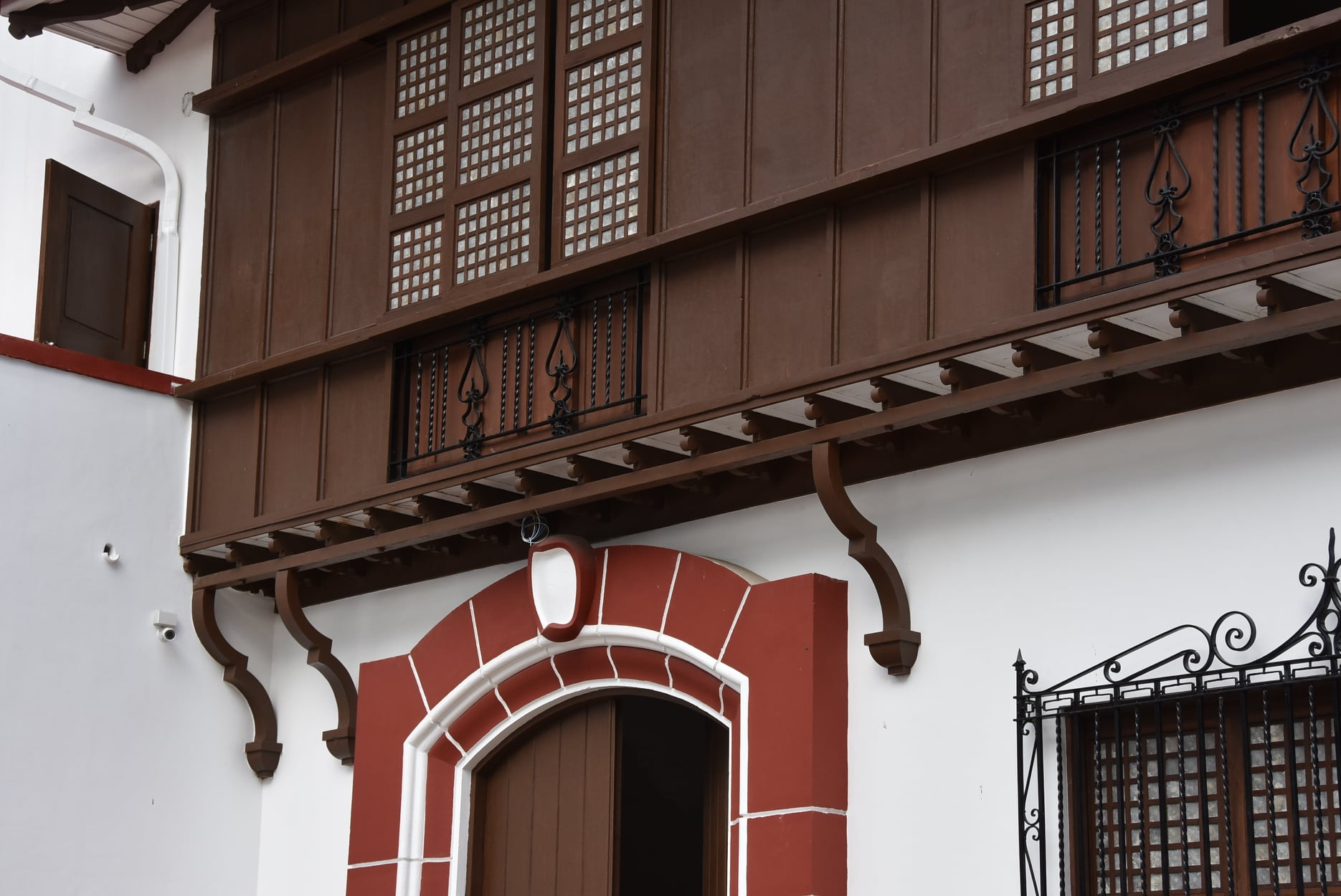 main entrance of the Presidencia showing intricate grillwork patterns and the overhanging wooden volada of the structure and capis shells on the windows