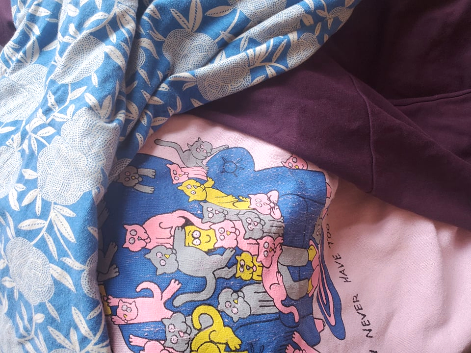 secondhand clothes including blue print dress, pink cat design crew neck jumper, and purple skirt