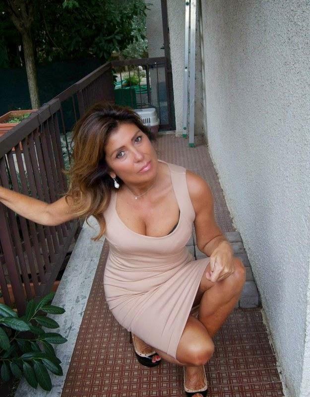Older woman wearing  low-cut dress showing her tits  kneeling in hallway