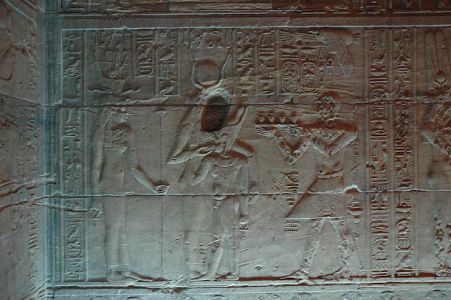 bajorrelieve en que se ve a Isis, con la cabeza borrada a martillazos, amamantando a un Horus niño grande