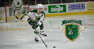 a hockey player in a Sioux City Musketeers uniform glides across the ice next to a Sioux City Musketeers logo