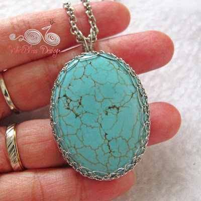 Close up of a large viking knitted turquoise pendant