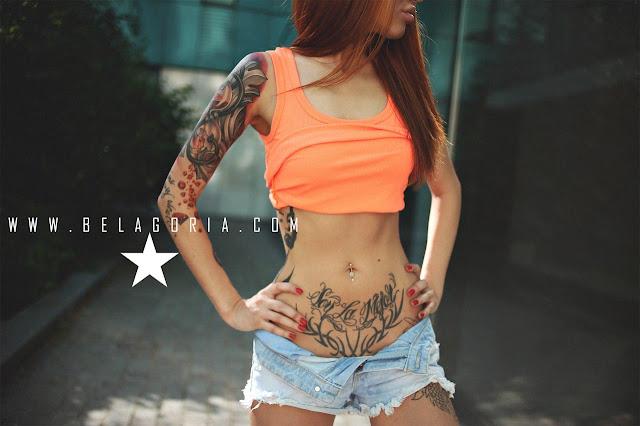 Vemos a una mujer con tatuajes tapando estrías en la barriga