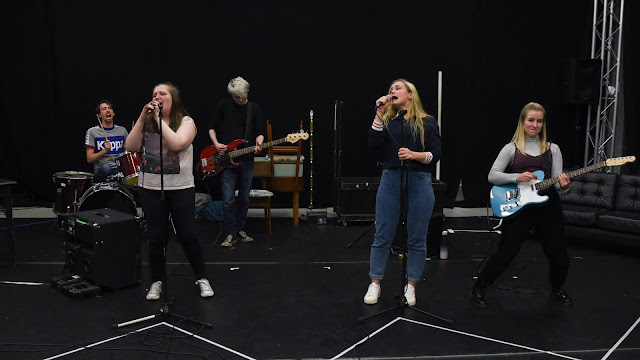 A band made up of five young people in a rehearsal room.