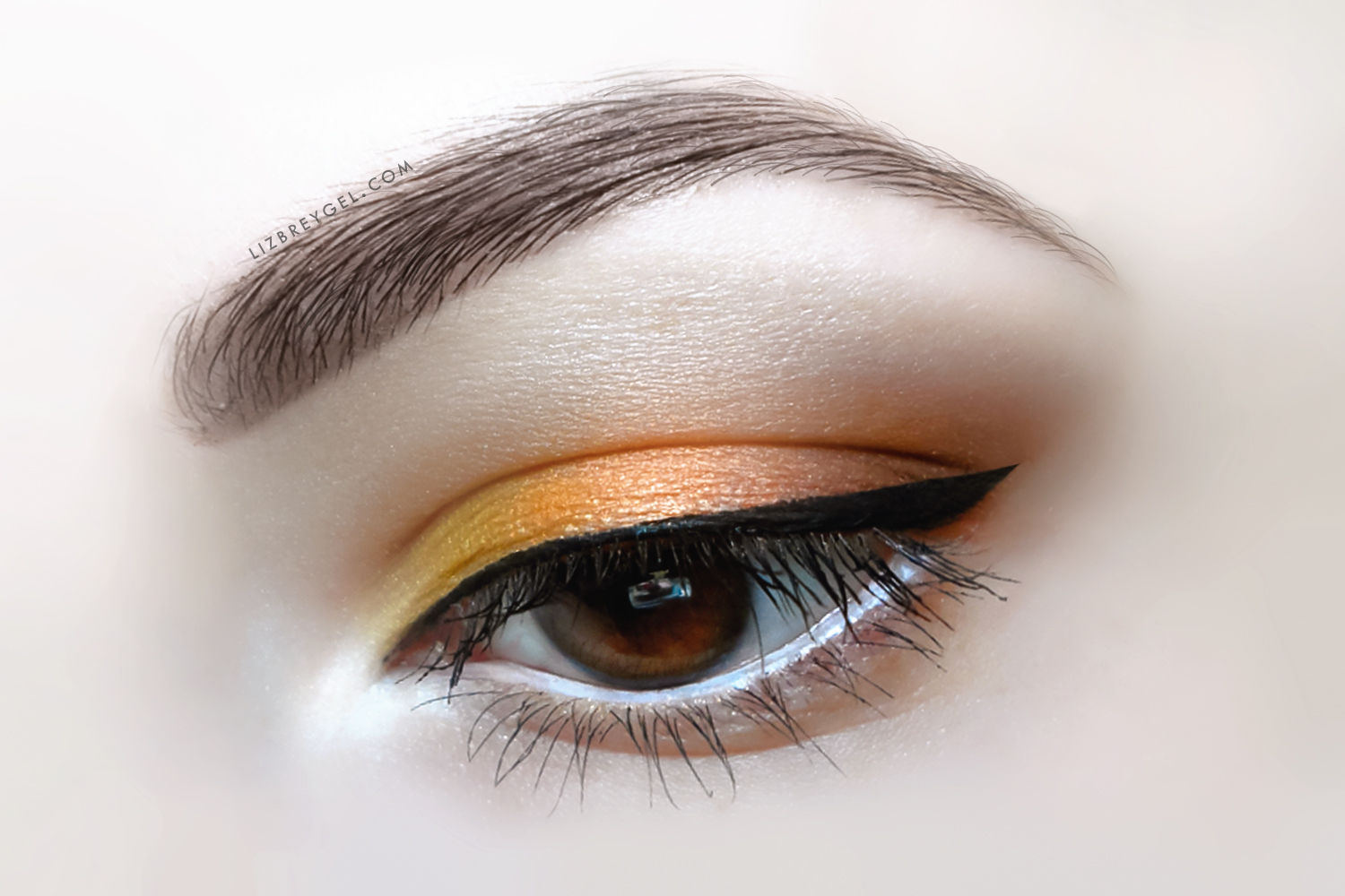 a close up picture of an eye with warm, autumn-inspired makeup look