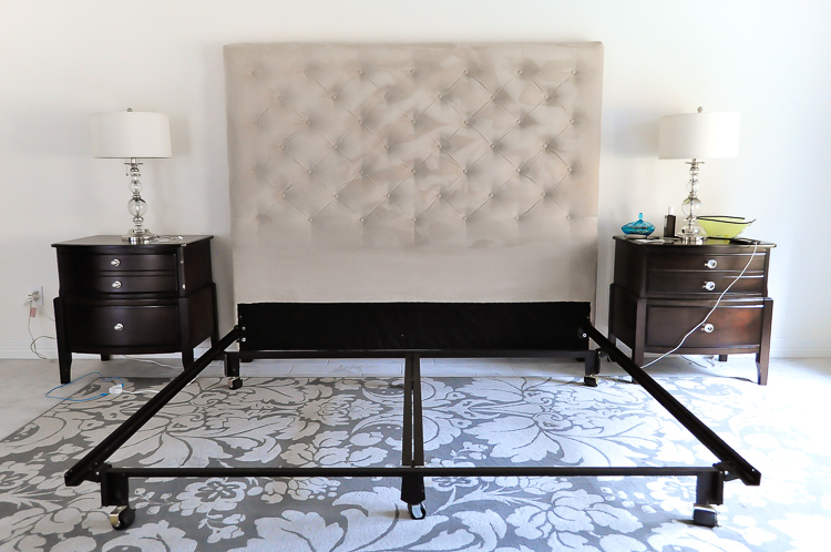 A large, tall tufted upholstered headboard is the centerpiece of this master bedroom.