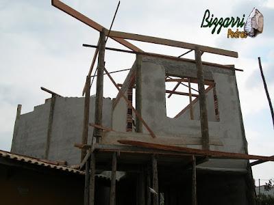 Obra com os pilares de madeira om a alvenaria de tijolo baiano e iniciando a execução do madeiramento já com as paredes com o reboque desempenado e filtrado tipo mão única de massa na parede.