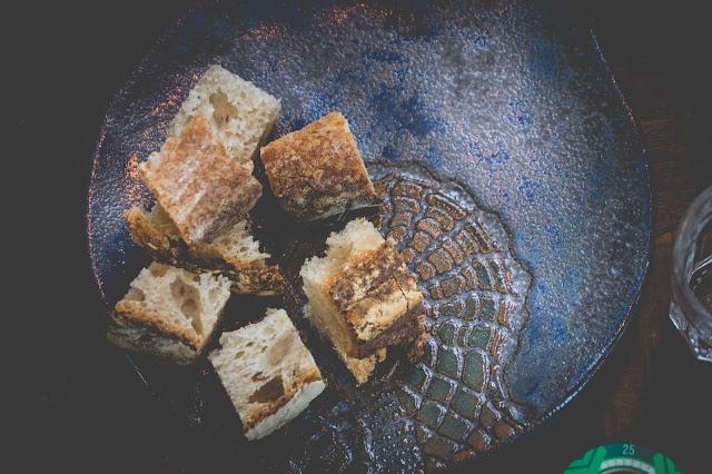 Pão rústico cortado em cubos no prato de cerâmica