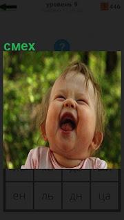 Маленький ребенок заразительно смеется, открыв рот и закинув головку