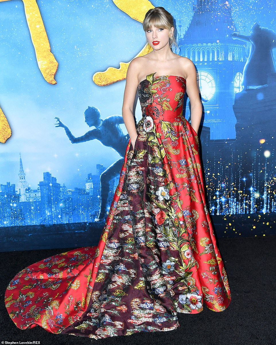Taylor Swift is an absolute vision in a red floral gown with crimson lipstick as she leads the stars at the premiere of the film Cats in New York City