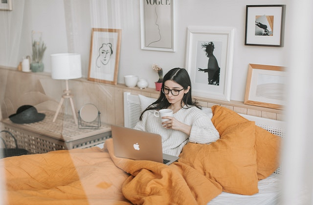 woman on bed with macbook and cup