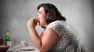 mujer obesa comiendo una hamburguesa