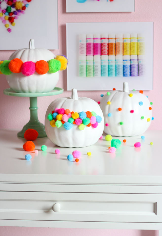 Decorate your pumpkins with pom-poms for modern and colorful Halloween decor!