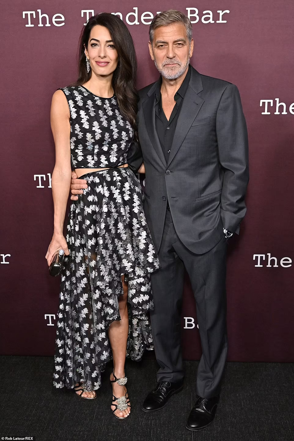 George Clooney looks classically handsome as he holds wife Amal close at the star studded premiere of his new film The Tender Bar in LA