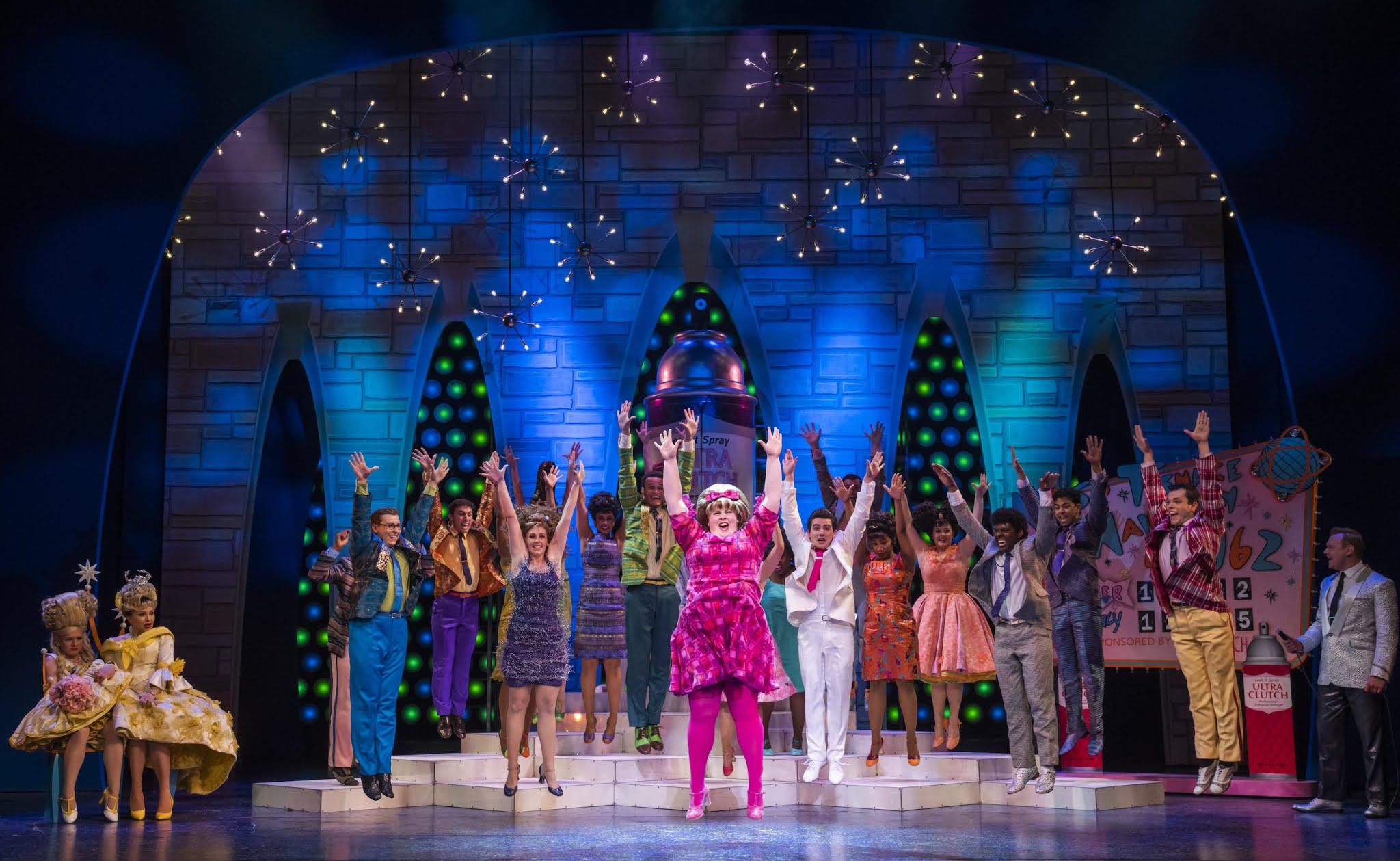 The cast of Hairspray the musical in the West End are performing on stage in 60s brightly coloured costumes, the cast is a mix of black and white performers with the character Tracy Turnblad leading them, wearing a pink dress.