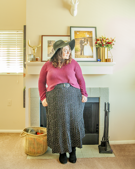 An outfit consisting of a black wide brim hat, a berry sweater half tucked into a black and white micro dot print maxi dress and black ankle boots.