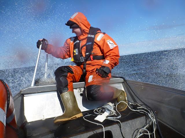Pelastautumispukuinen henkilö veneen keulassa veden roiskuessa ympärillä