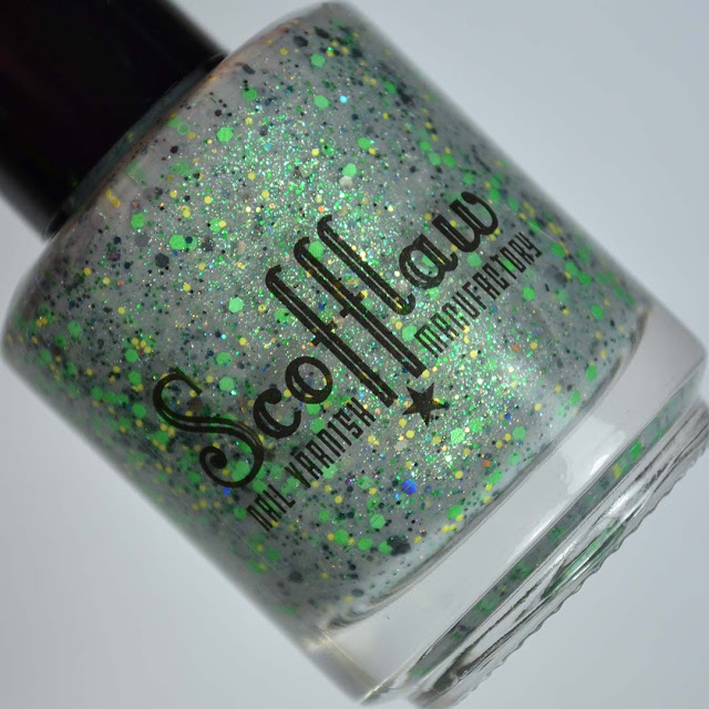grey nail polish with green glitter in a bottle