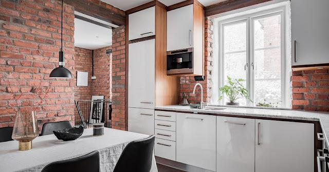 Dormitor la subsol și cărămidă expusă într-un apartament pe două niveluri din Stockholm