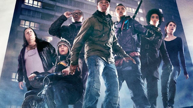 Movie still from Attack the Block showing a group of teens in front of a building, wearing leather jackets and jeans, looking up at some unseen threat, in defensive stances, ready to rumble