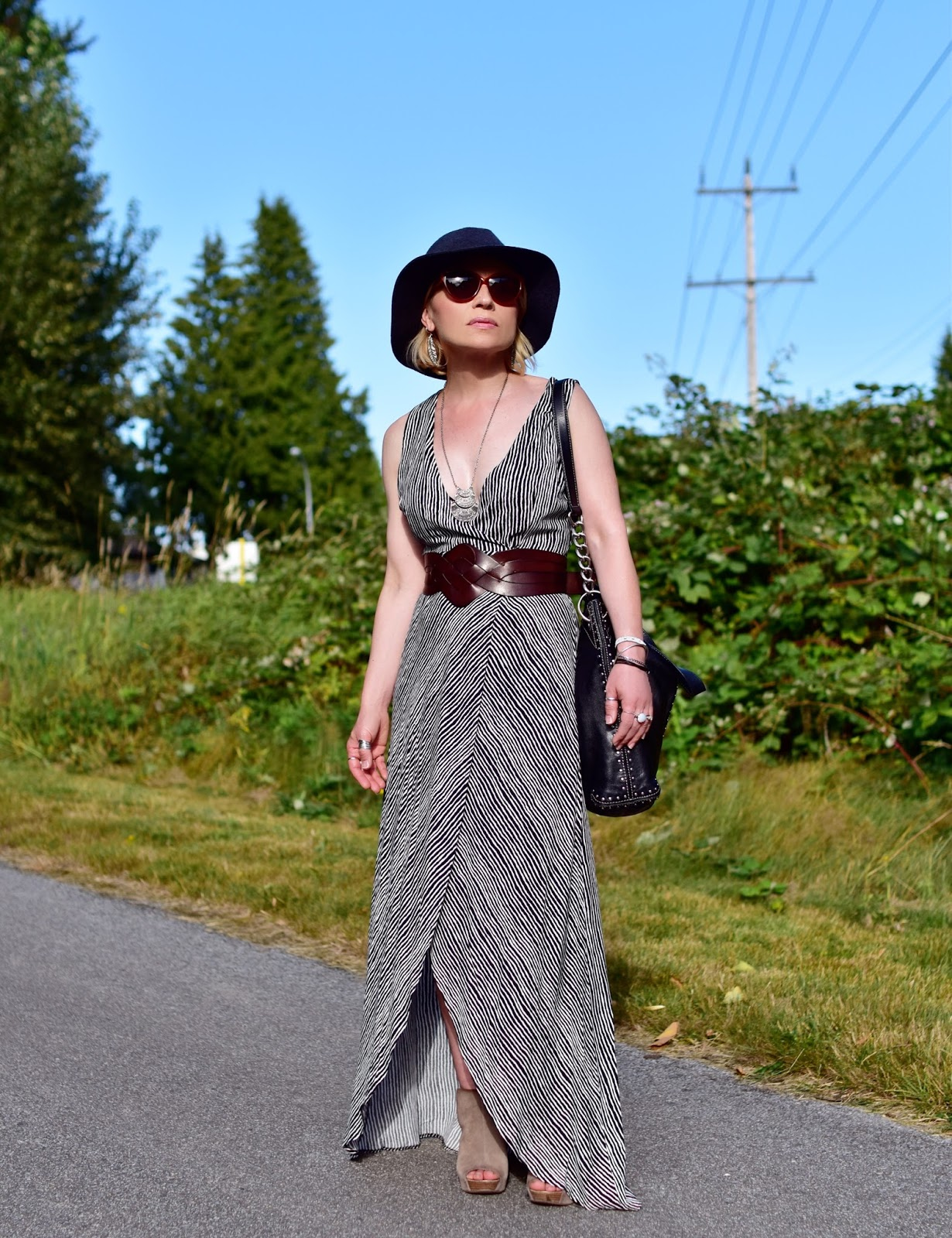 Monika Faulkner styles a striped maxi-dress with a corset belt, open-toe wedge booties, and a floppy hat