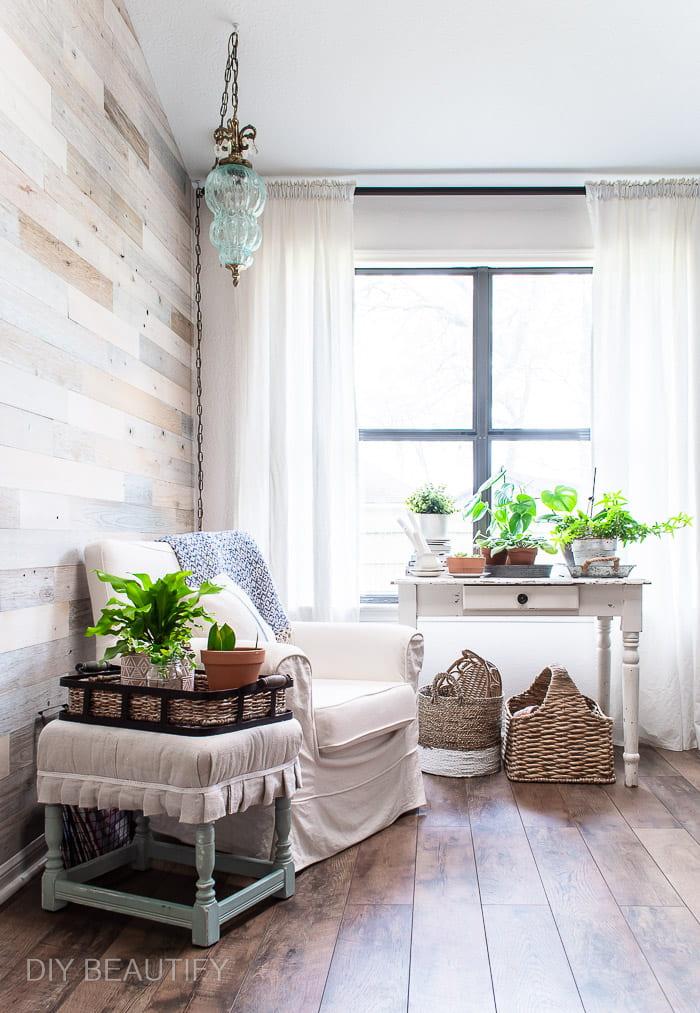 sunroom with wood floors, reclaimed wood walls, and houseplants
