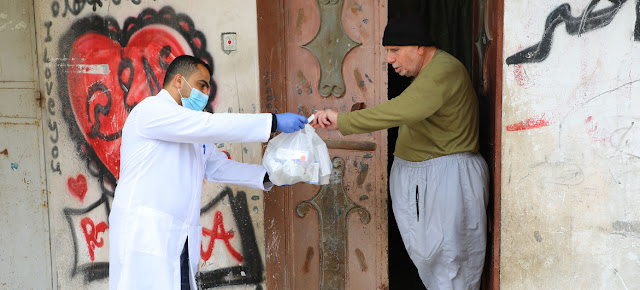 Un trabajador de UNRWA le ayuda con medicamentos a un anciano palestino en la Franja de Gaza.© UNRWA/Khalil Adwan