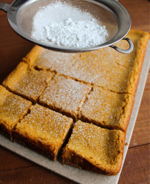 sifting powdered sugar over chilled pumpkin gooey butter cake
