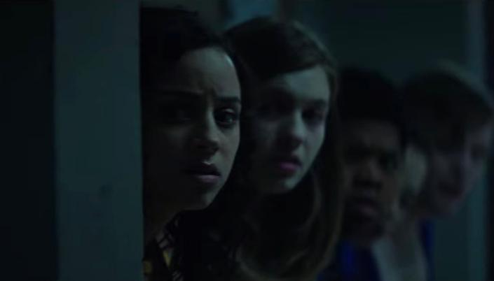 Imagem: os personagens do elenco principal do filme, escondidos atrás de uma pilastra num corredor, da direita para a esquerda, a personagem Deena, uma garota latina, com cabelos pretos cacheados, Sam, uma garota branca com cabelos claros e muito pálida, Josh, um garoto negro e baixo, e Simon e Kate, fora de foco.