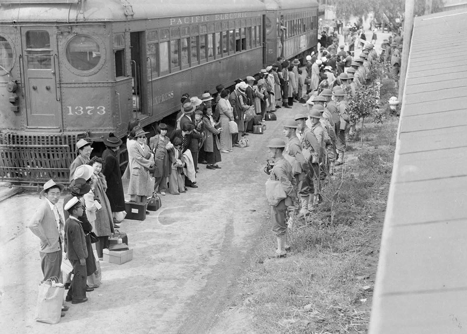 Personas de ascendencia japonesa de San Pedro, California, llegan al centro de la Asamblea de Santa Anita en Arcadia, California, en 1942. Los evacuados vivían en este centro en la pista de carreras de Santa Anita antes de ser trasladados tierra adentro a otros centros de reubicación.