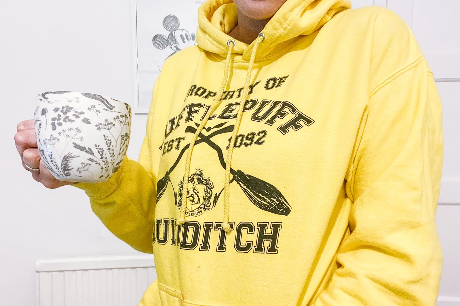 Girl wearing a yellow Hufflepuff hoodie holding a mug of tea.