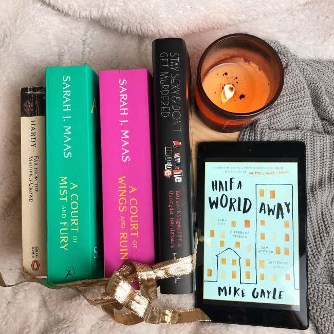 Stack of books facing spine up next to a kindle showing the cover for 'Half a World Away' by Mike Gayle