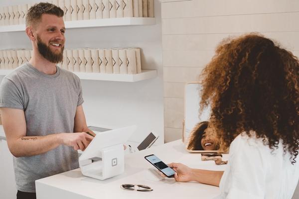 Vendedor e cliente passando o cartão de crédito em uma loja