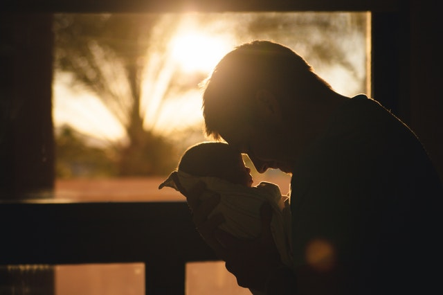 A silhouette of a father and his baby
