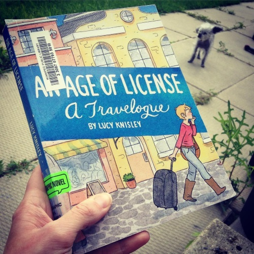 A pale hand holds a paperback copy of An Age of License. Its cover features a drawing of a ginger white girl pulling a suitcase past some Scandinavian storefronts. Behind the book, Murchie stands on a concrete patio. He has one ear raised.