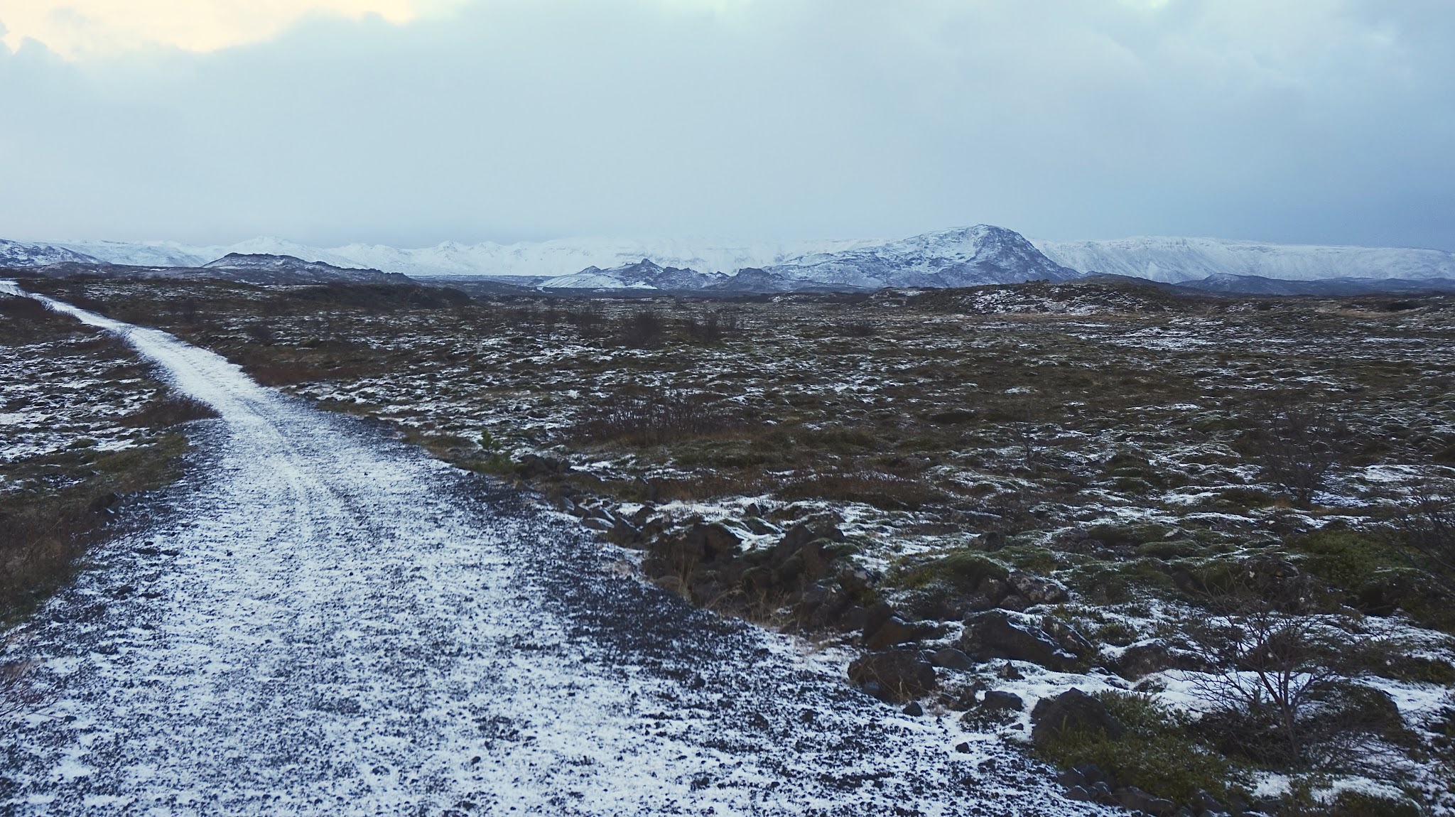 snowy path leading up to snowy mountains, moody sky
