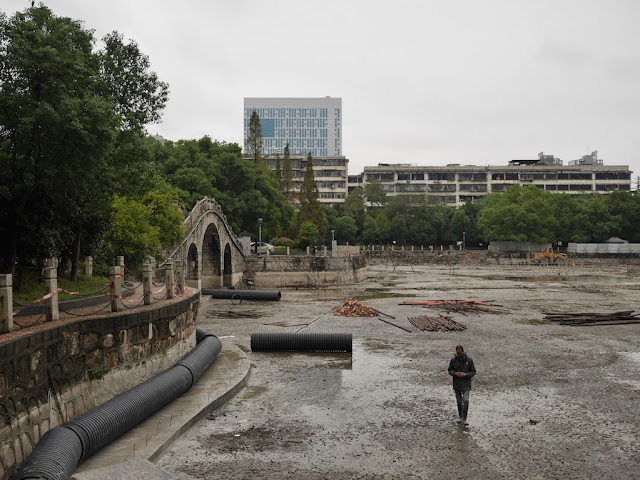 man walking in drained lake at Lianhu Square (莲湖广场) in Hengyang