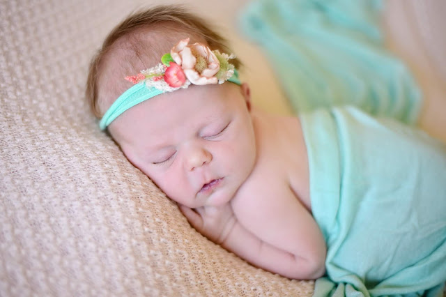 newborn girl on beige blanket with mint details