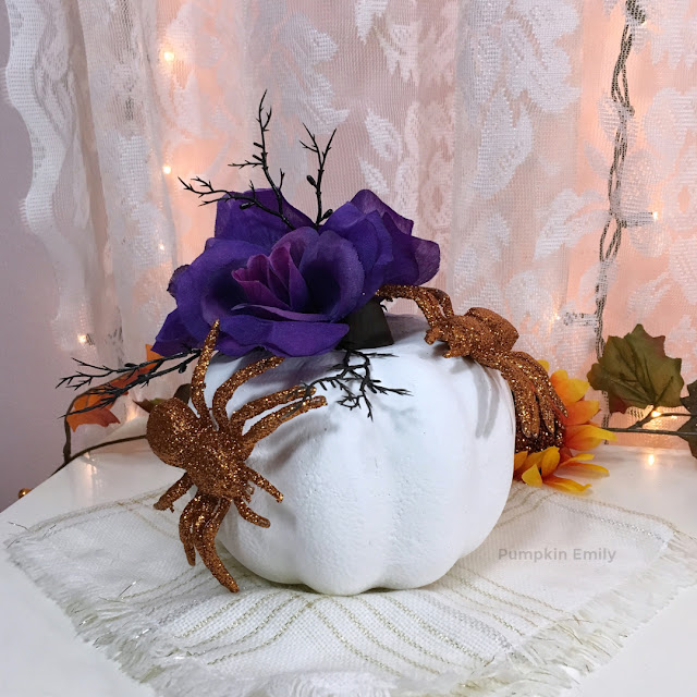 pumpkin with flowers and spiders on it