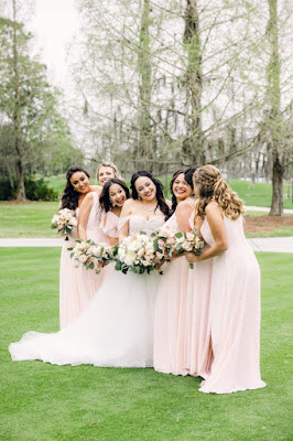 bride and bridesmaids in pink dresses smiling