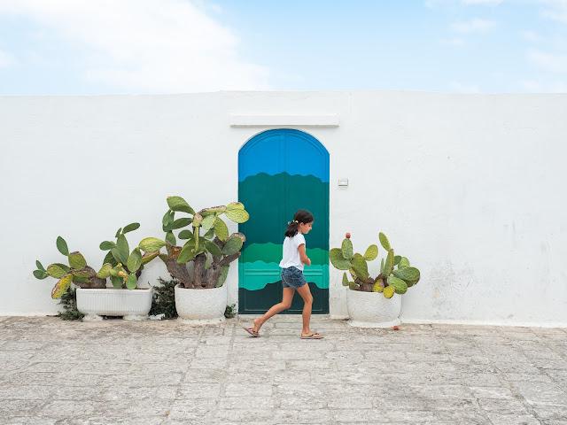 Niña pasando frente a una pared blanca con puerta verde y cactus